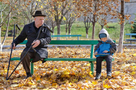 Elderly handicapped man with crutches watching a young boy as the two share a wooden bench in the park as the youngster plays with his tablet computer surfing the internet photo