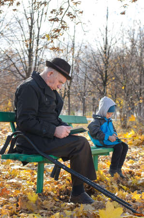 Retired disabled man on crutches sitting reading a book in the park with his grandson sitting at the other end of the bench playing on his tablet computer photo