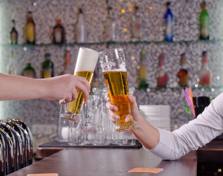over the counter: Two men toasting each other with their beers clinking their glasses over the counter as they celebrate together Stock Photo