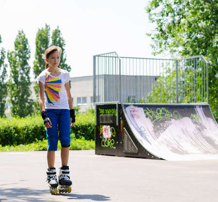 Pretty teenage girl skates and protective leather mitts standing at the skate park in front of a cement jump or ramp photo