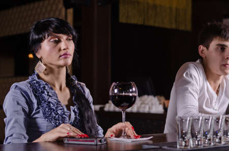 inebriated: Inebriated young woman sitting at a bar with a morose expression and a large glass of red wine in front of her