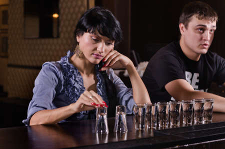 strangers: Lonely woman alcoholic sitting at a bar counter with a long line of full shot glasses staring morosely at the counter as she drinks her way through them
