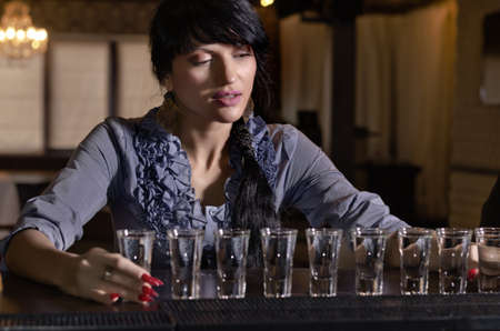 morose: Attractive young woman sitting drinking heavily at a bar with a long row of shot glasses full of alcohol lined up in front of her Stock Photo