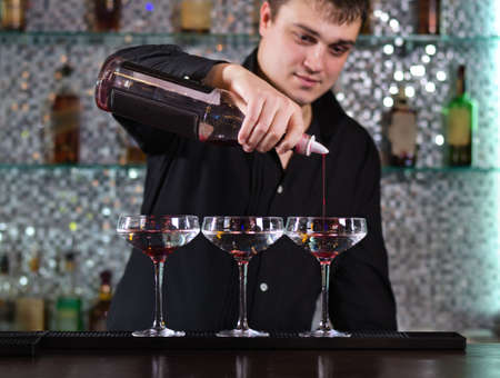 Handsome young male barman mixing cocktails at the bar standing pouring into a row of three glasses Stock Photo