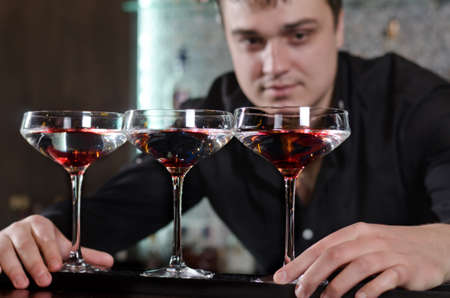 aligning: Professional young bartender measuring and aligning three saucer glasses of red wine on the bar
