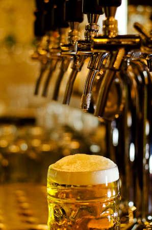 Close up van een pul bier met een schuimige witte kop staande op een bar in een cafe met selectieve focus op het glas