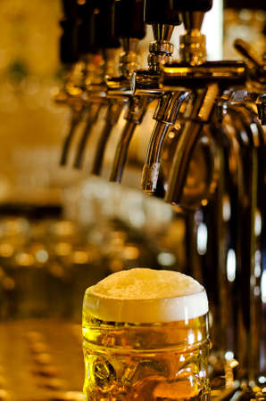 Close up view of a tankard of beer with a frothy white head standing on a bar counter in a pub with selective focus to the glass