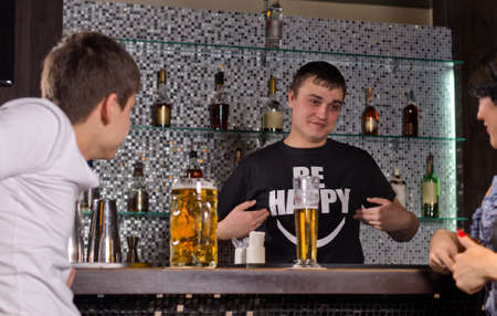 Friendly young male barman serving customers at the bar counter smiling and gesturing with his hands as he chats to a woman photo