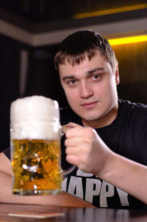 litre: Young man in a pub holding up a very large litre tankard of beer with a good frothy head with focus to the glass