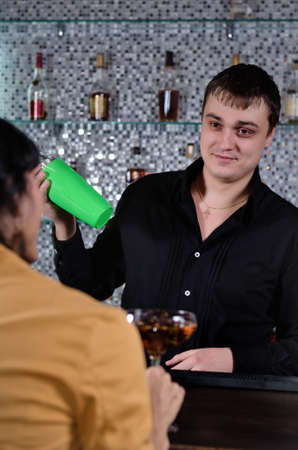 courting: Woman sitting at a bar waiting to be served as the barman mixes her a cocktail