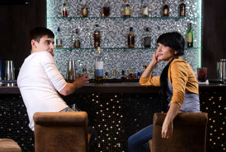 barstools: View from behind of a young man and woman chatting at the bar turning to face each other on their barstools as they spend a relaxing evening at a nightclub Stock Photo