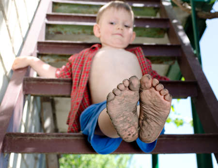 Little boy showing off his dirty feet sitting on a step holding them out to the camera with their muddy soles after playing barefoot in the garden photo