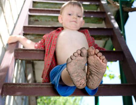 piedi nudi ragazzo: Ragazzino che mostra fuori i suoi piedi sporchi seduto su un gradino tenendo fuori la telecamera con le loro suole di fango dopo aver giocato a piedi nudi in giardino