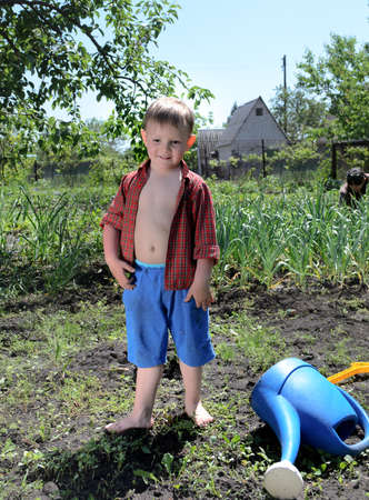 Happy little boy working in the garden standing in the summer sun alongside the watering can in the vegetable patch on a rural smallholding photo