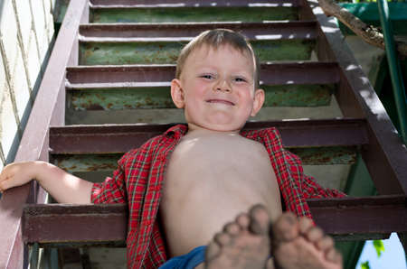 dirty feet: Little boy showing off his dirty feet sitting on a step holding them out to the camera with their muddy soles after playing barefoot in the garden Stock Photo