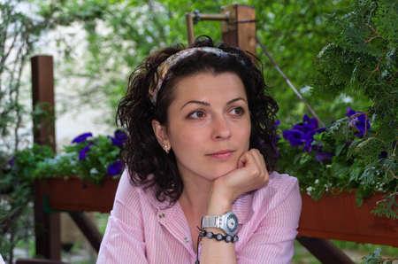 Aantrekkelijke brunette vrouw zittend aan een tafel buiten op een lommerrijke groene patio kijken naar iets uit aan de rechterkant van het scherm Stockfoto