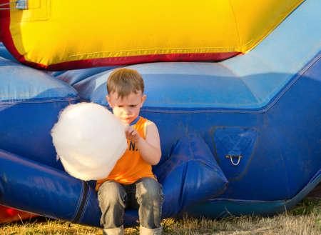 algodon de azucar: Pequeño muchacho lindo que disfruta de un palo de algodón de azúcar comiendo mientras estaba sentado en un castillo inflable de plástico en un parque de atracciones