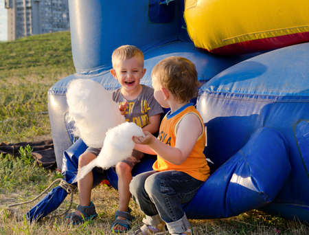 Two little boys eating candy floss laughing with enjoyment as they sit together on a plastic jumping castle at a funfair