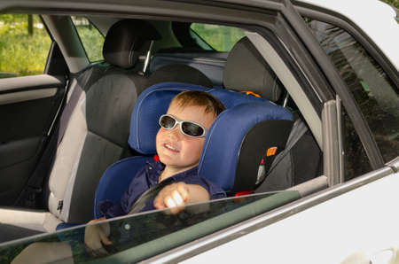 Little boy in trendy sunglasses relaxing in the back of a car in a child safety seat as he waits for his parents , view through the back passenger window photo