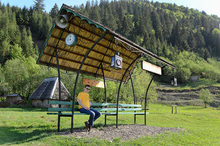 Man sitting on a covered bench in a field with an attached clock and loudspeaker against a backdrop of forested mountains and a timber cabin photo