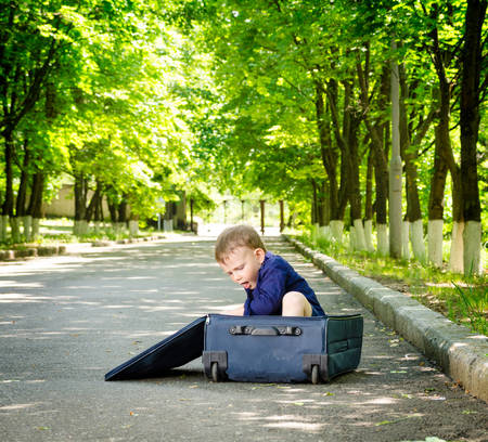 exuberant: Young boy playing with an open suitcase on a rural road climbing inside as he waits in the shade of leafy green trees