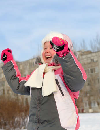 vivacious: Beautiful vivacious laughing little girl cheering with her hands raised as she plays in the fresh snow on a cold winter day