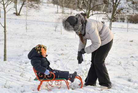 Mother and son tobogganing in the snow with the little boy sitting on the sled as his mother pulls it along in a wintry landscape photo