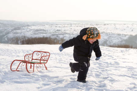 Little boy running through snow dragging a colourful orange toboggan behind him as he enjoys his freedom in the winter countryside photo