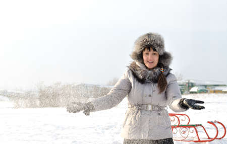 exhilarated: Happy woman tin a fashionable fur lined jacket standing a beautiful winter landscape throwing snow into the air