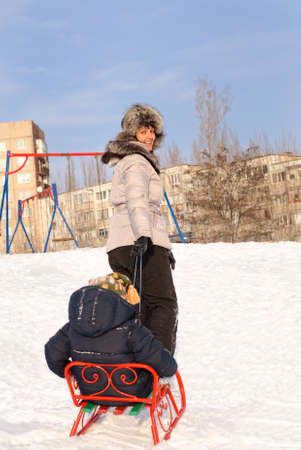 Rear view of a mother pulling a toboggan with her child riding on it through the snow in a cold rural winter landscape as they trudge back up a gentle slope for a new run photo