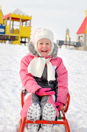 Pretty little girl dressed in a fashionable warm pink winter\ outfit playing on a sled in the snow reclining on her back smiling\ happily at the camera
