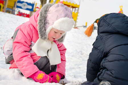 anorak: Adorable little girl in a trendy pink winter outfit bending down gathering snowballs in the snow Stock Photo