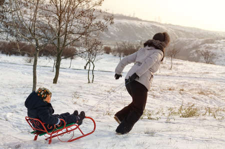 Mother running through the snow with a sled pulling her little son along behind her in a cold winter landscape photo
