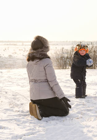 Small boy taking aim and throwing a snowball at his mother as she kneels down in the winter snow as they play together enjoying the winter weather photo