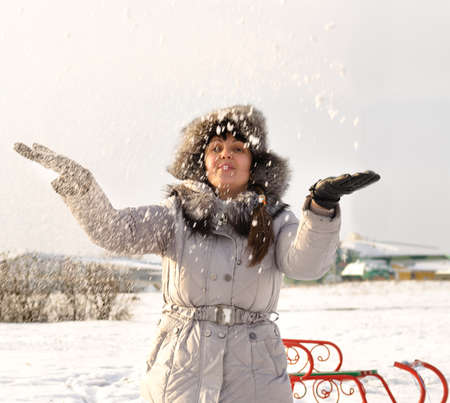 Happy woman tin a fashionable fur lined jacket standing a beautiful winter landscape throwing snow into the air