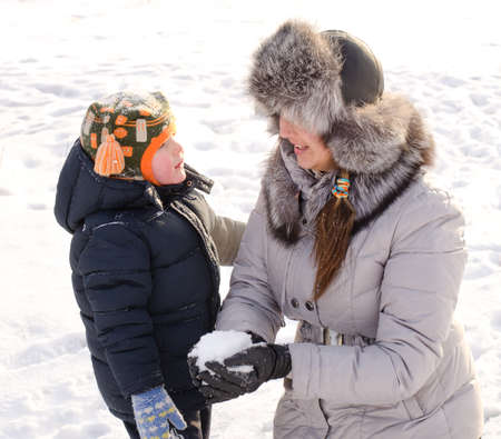 Cute little boy playing with his mother in the snow stretching up to touch her furry cap as she kneels down with a smile for him to reach her photo