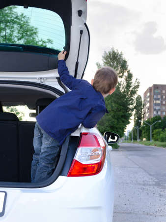 Little boy leaning out of the back of a hatchback car parked at the side of an urban street as he watches and waits for someone Reklamní fotografie