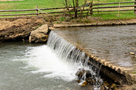 weir: Water in a stream cascading over a small weir bordered by a paddock with a rustic wooden fence