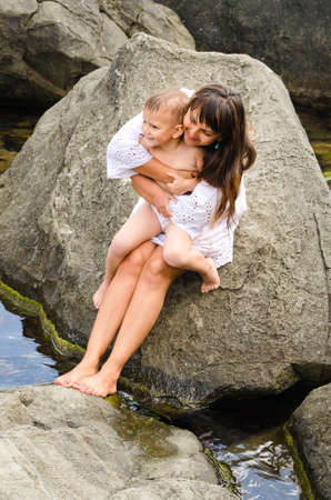to lap: a loving young mother and her son sitting on a rock at the seaside with the little boy sitting on her lap as they smile and cuddle