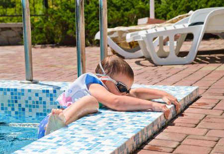 buoyancy: Peque�o ni�o trepando fuera de una piscina agarrando la repisa para transportar a s� mismo con su chaqueta de flotabilidad y gafas
