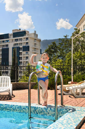 Happy little boy waving at the camera poolside as he stands on the steps at the edge of the swimming pool ready to take a dip Stock Photo