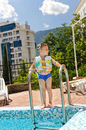 buoyancy: Peque�o muchacho que espera para ir a nadar en la piscina de pie en la parte superior de los pasos con sus googlies y chaqueta de flotaci�n listos para saltar al agua fr�a y azul Foto de archivo