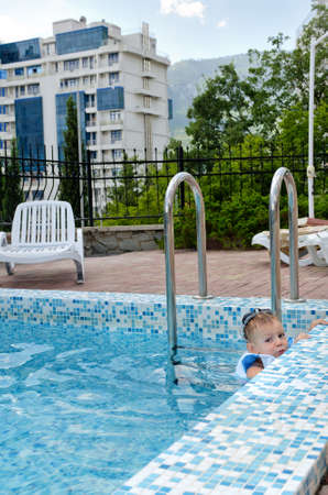 pool preteen: Little boy swimming in a pool hanging onto the tiled edge as he enjoys the cool water while waiting for his mother to join him