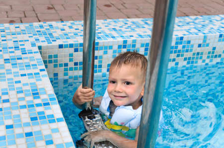 buoyancy: Cute little boy enjoying a swim in the cool water of a swimming pool hanging onto the metal steps in his buoyancy jacket on a hot summer day