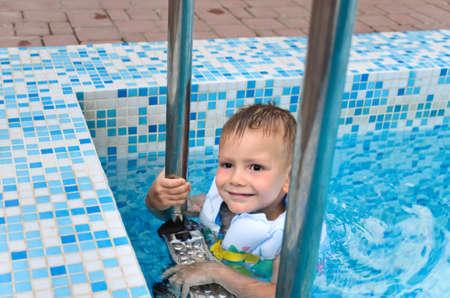 buoyancy: Ni�o lindo disfrutando de un ba�o en el agua fr�a de la piscina que cuelga sobre los escalones de metal en su chaqueta de flotaci�n en un d�a caluroso de verano
