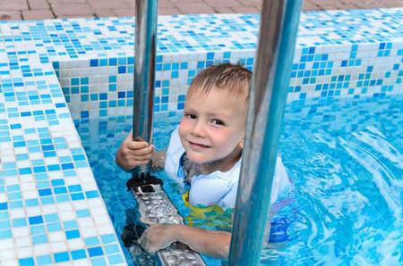 buoyancy: Ni�o lindo disfrutando de un ba�o en el agua fresca de una piscina que cuelga sobre los escalones de metal en su chaqueta de flotaci�n en un d�a caluroso de verano