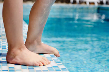 Young child standing barefoot at the edge of a swimming pool, closeup view of the legs