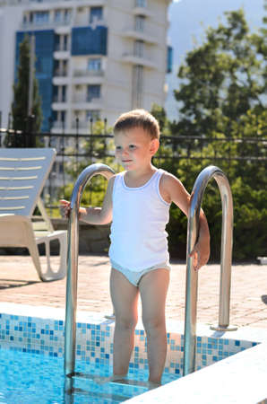contemplated: Cute little boy standing on swimming pool steps as he contemplated the cool water on a hot summer day with a smile of anticipation