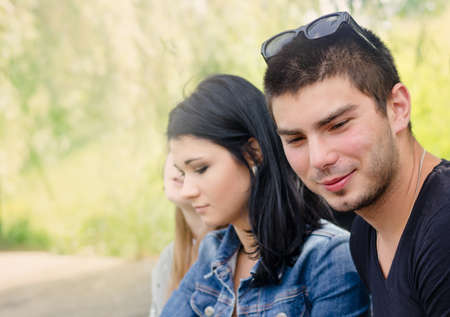 Handsome trendy young man with an amused smile sitting alongside his pretty girl fiend with his sunglasses pushed to the top of his head as they sit outdoors in a park with a female friend Stock Photo - 26710884