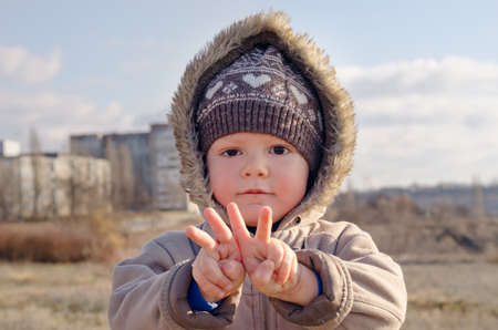 Cute young boy ina warm furry winter hooded jacket standing in the sunshine making V-sign gestures with his hands for peace or victory photo